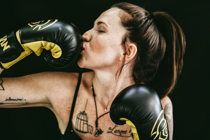 A woman with tattoos and her hair in a pony tail kissing her boxing gloves