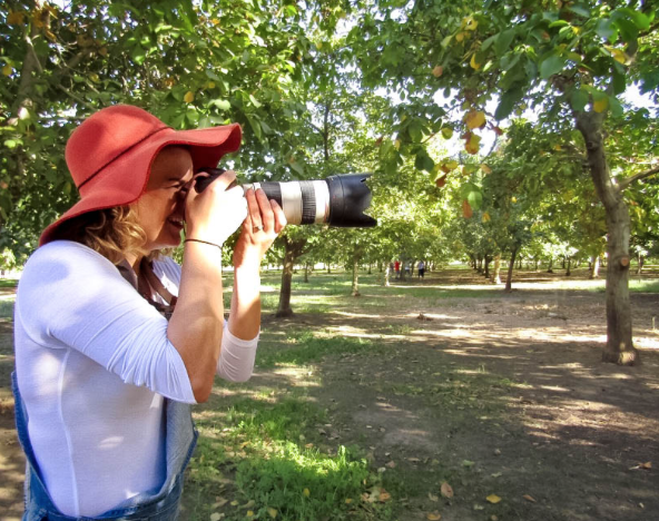 Christa Boynton holding camera to her eye in orchard