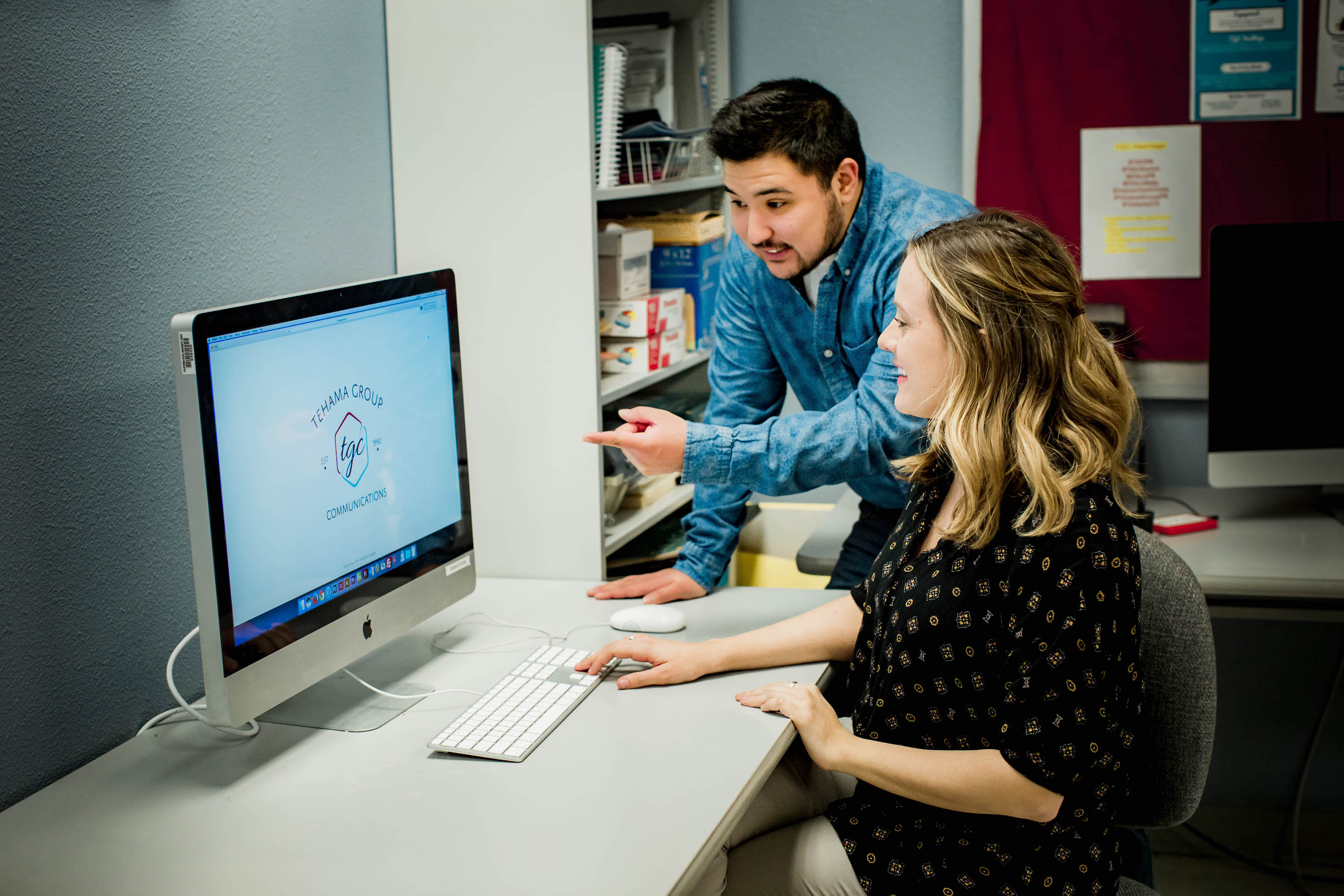Jae Siqueiros and Kelsey Veith look at a T-shirt design on the computer screen smiling
