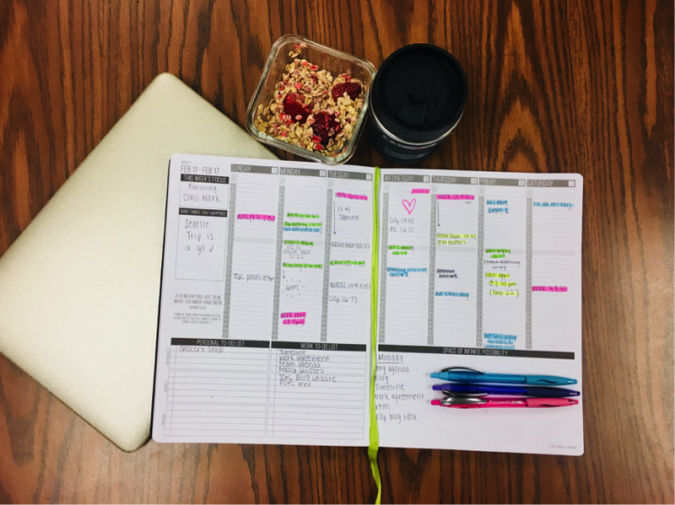 An organized, color coded planner with granola and coffee beside it with a note pad