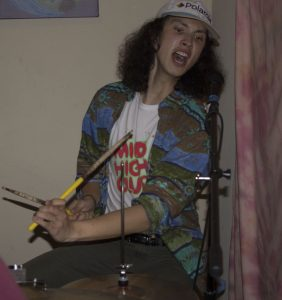 A man in a polaroid baseball cap playing the drums.