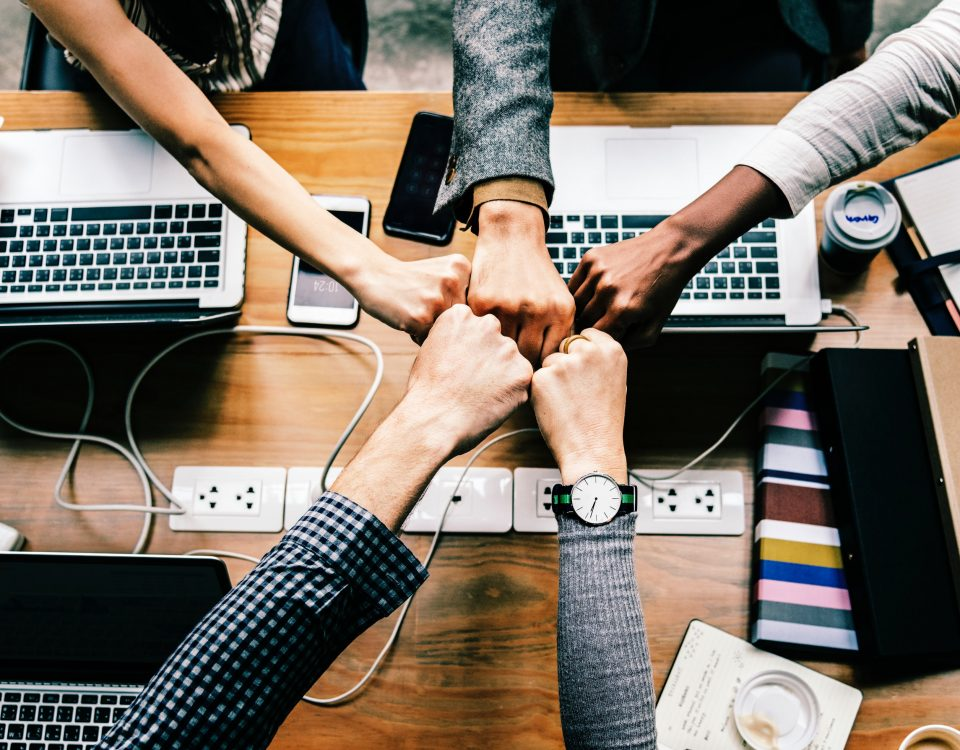 A photo of five hands fist bumping each other over a table of binders, notebooks, smartphones, and laptops.