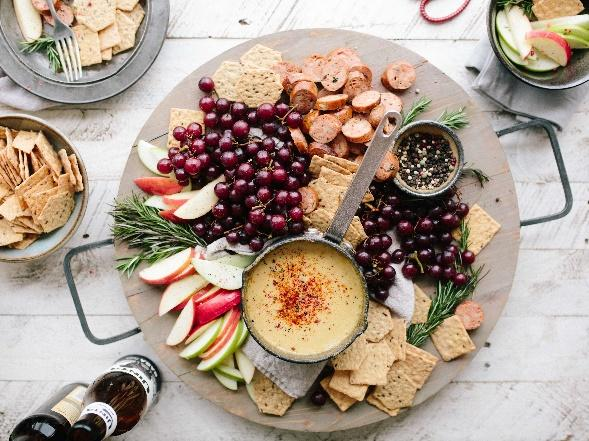 A photo of an assortment of fruit and other food on a plate with a bottled drink to accompany it
