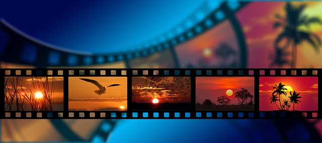 A strip of camera film against a blue background, gives the illusion that the film is moving, on the film there are three pictures of sunsets are are orange