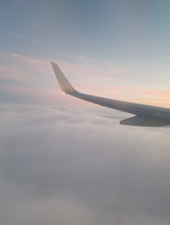 A plane flying through clouds with a sunset in distance.