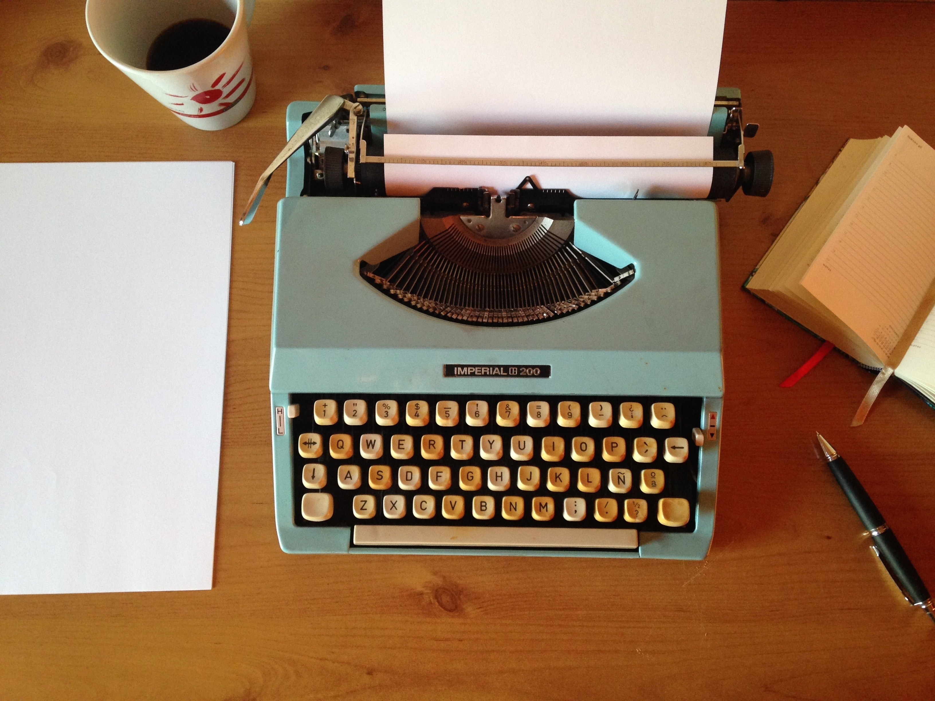 Picture of a teal typewriter on a wooden table with a cup of coffee, pens and stationary by it.
