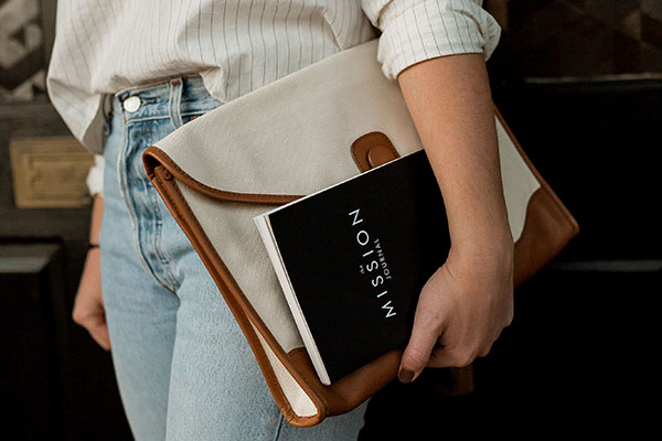 Photo by David Iskander on Unsplash, A woman holding a handbag and book